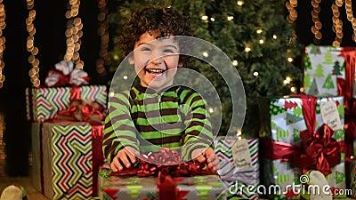 El niño lindo recibe el regalo de Navidad almacen de video