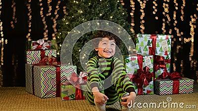 El niño lindo se sienta emocionado delante del árbol de navidad metrajes