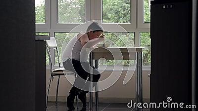 El niño pequeño gordo hambriento se sienta en cocina en la tabla con apetito come la sopa en el fondo de la ventana Concepto de m almacen de video