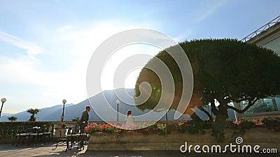 El novio feliz corre a su novia en la terraza del verano Lale Como, Italia honeymoon almacen de metraje de vídeo