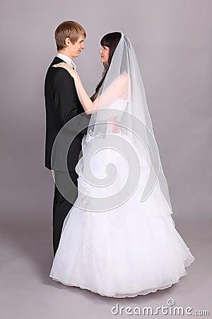 El novio y la novia abrazan y miran uno a
