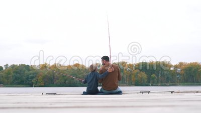 El padre y el hijo están pescando en el embarcadero almacen de video