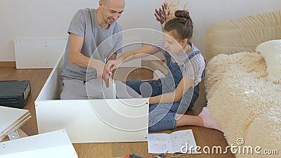 El padre y su hija adolescente montan un nuevo rack en el apartamento metrajes