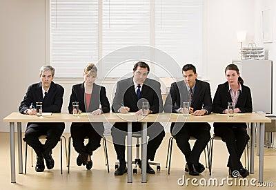 El panel de los compañeros de trabajo alrededor para conducir una entrevista