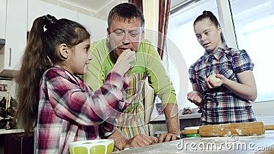 El pap? se divierte con sus hijas mientras que cocina la pasta en su cocina casera almacen de video