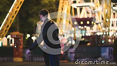 El par bonito atractivo pasa noche de la fecha en el parque de atracciones en la noche almacen de video