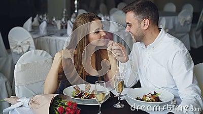 El par cariñoso feliz está llevando a cabo las manos, está hablando y se está besando durante cena romántica en restaurante cariñ almacen de video
