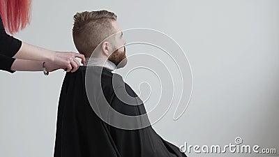 El peluquero de sexo femenino pelirrojo joven está cortando el pelo del cliente barbudo del hombre metrajes