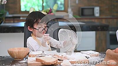 El pequeño muchacho asiático lindo que tamiza la harina de la pasta con el colador del tamiz del tamiz en la cocina casera para s almacen de metraje de vídeo