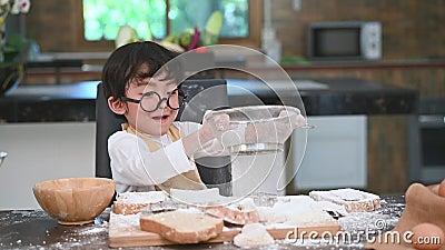 El pequeño muchacho asiático lindo que tamiza la harina de la pasta con el colador del tamiz del tamiz en la cocina casera para s metrajes