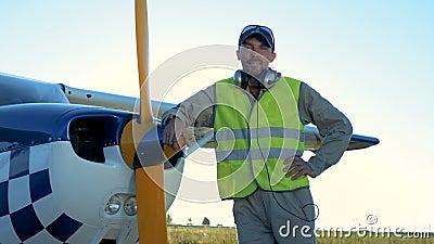 El piloto de sexo masculino se coloca cerca de un aeroplano privado ligero Una persona se coloca cerca de un pequeño avión, miran almacen de metraje de vídeo
