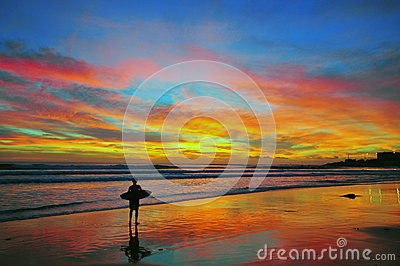 El practicar surf en puesta del sol