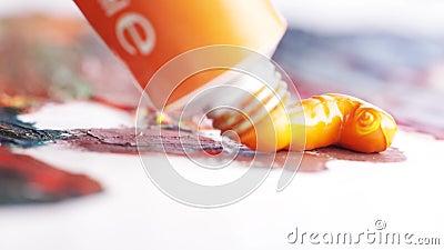 El primer de la pintura de aceite anaranjado presionó del pequeño tubo en la lona pintada acci?n Artes y conceptos de pintura metrajes