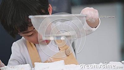 El primer del pequeño muchacho asiático lindo que tamiza la harina de la pasta con el colador del tamiz del tamiz en la cocina ca almacen de metraje de vídeo