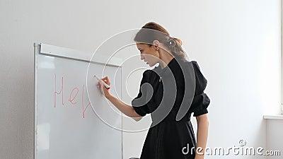 El profesor escribe una palabra sobre ayuda almacen de video