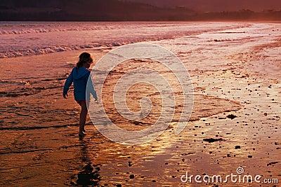 El recorrer de la playa de la muchacha