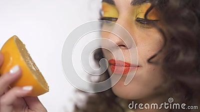 El retrato ascendente cercano de la muchacha rizada joven con brillante compone la lamedura del pedazo jugoso maduro de naranja c metrajes