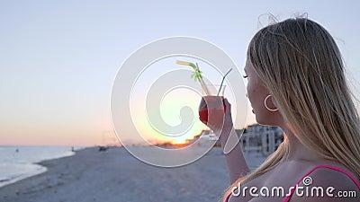 El retrato de la hembra joven en el contraluz, muchacha bebe el cóctel almacen de video
