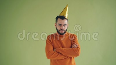El retrato del hombre trastornado en el sombrero del partido que se colocaba solamente con los brazos cruzó el suspiro almacen de video