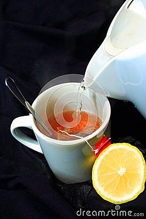 El té caliente del limón vierte