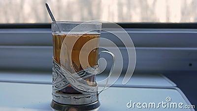 El té en el soporte de vaso está en la tabla en el compartimiento del tren almacen de video