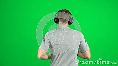 El tipo con grandes audífonos está corriendo, Chroma Key Vista posterior almacen de metraje de vídeo
