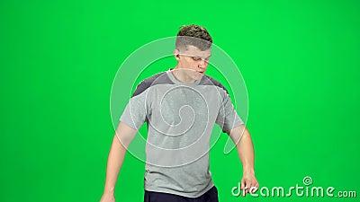 El tipo va y baila, sonríe y se regocija en una pantalla verde, Chroma Key Vista lateral metrajes