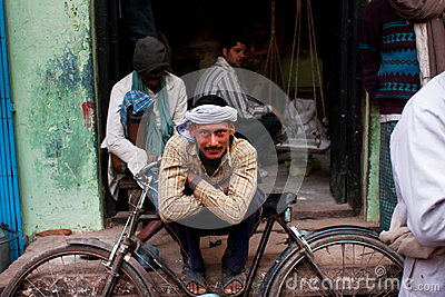 El trabajador en un turbante descansa inclinarse en su bicicleta retra en la calle Imagen de archivo editorial