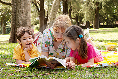 Elder sister reads to children of the book