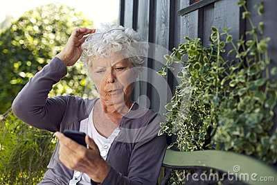 Elder woman reading text message on her cell phone