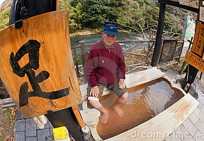 Elderly Asian Man Soaking his feet at a hotspring Editorial Image