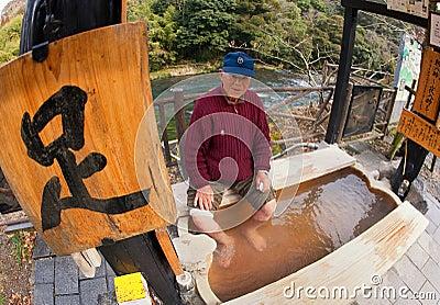 Elderly Asian Man Soaking his feet at a hotspring Editorial Image