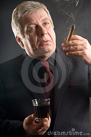 Elderly businessman with drink and cigar, smoking