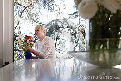 Elderly caucasian woman with flowers at home