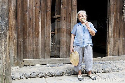 Elderly Chinese Lady Eating Cucumber