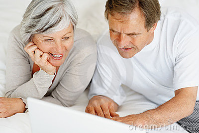 Elderly couple browsing the internet while in bed