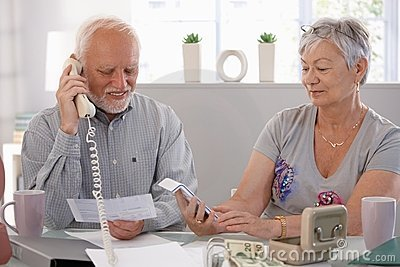 Elderly couple checking bills at home