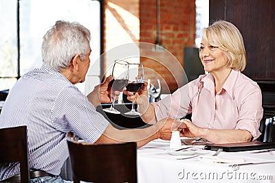 Elderly couple clink glasses