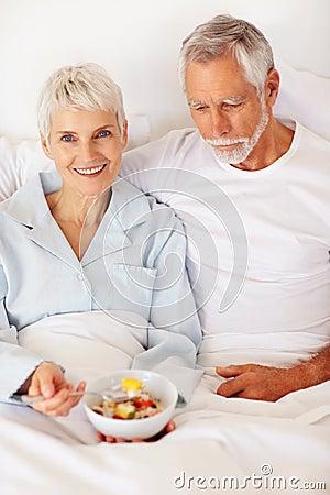 Elderly couple enjoying a bowl of fruits