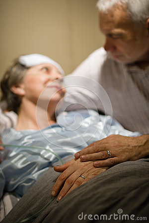 Elderly couple holding hands at clinic ward