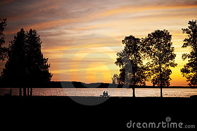 Elderly couple sitting on a bench by lake at sunse