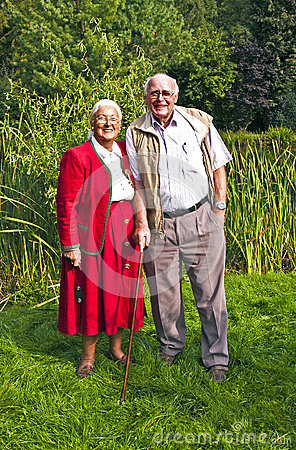 Elderly couple standing hand in hand in their garden