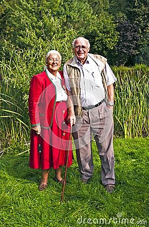 Elderly couple standing hand in hand in their garden