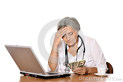 Elderly doctor with dollars Stock Photo