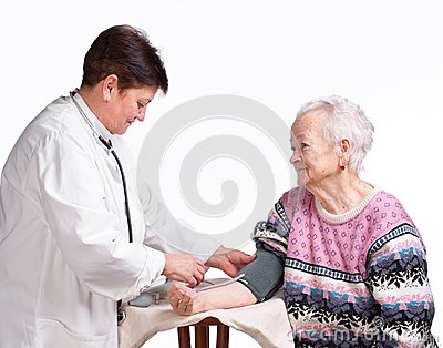 Elderly doctor and patient . Measuring pressure.