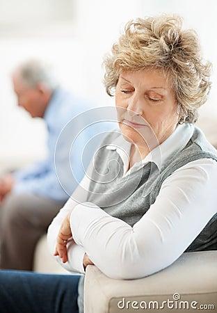Elderly female sitting on sofa with a man