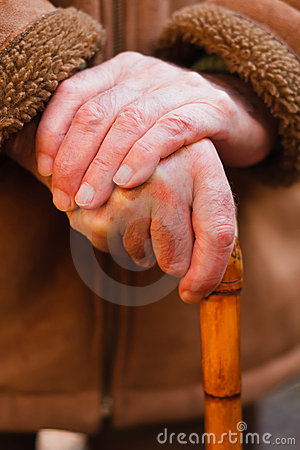 Elderly hands resting on walking stick