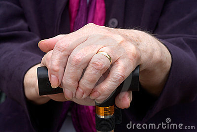 Elderly hands on walking stick