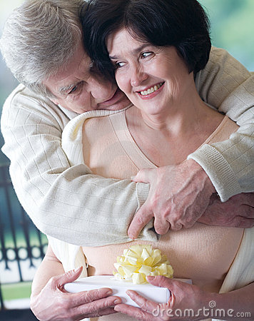 Elderly happy couple with gift box