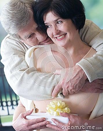 Elderly happy couple with gift box